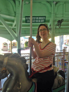 Photo of student from Corliss Institute riding a painted horse on a carousel